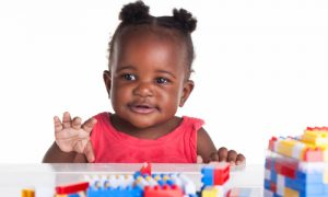 toddler girl is playing with her blocks on the table