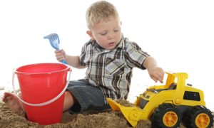 toddler playing with toy bulldozer