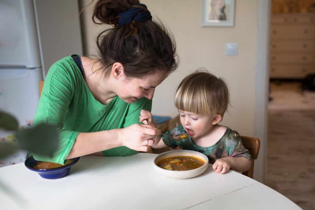 caregiver feeding a baby with soup
